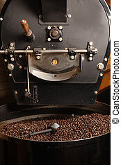 The freshly roasted coffee beans from a large old coffee roaster being stirred in the cooling cylinder.