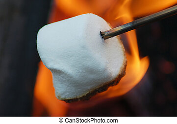 A roasted marshmallow roasting over a fire