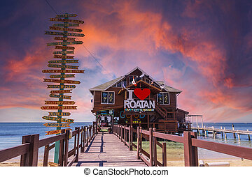 Roat?n, Honduras ?; January 2020: a wooden bar over the sea at West End Beach on the island of Roatan at sunset