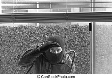 Robber and theif - A robber peers through a window to see if...