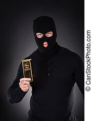 Robber holding a gold bullion bar - Robber disguised in a ...