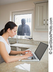Robber observing a young woman in the kitchen