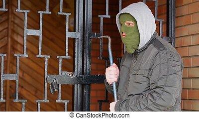 Robber with crowbar near gates