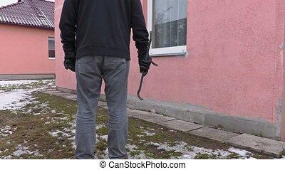Robber with crowbar near house