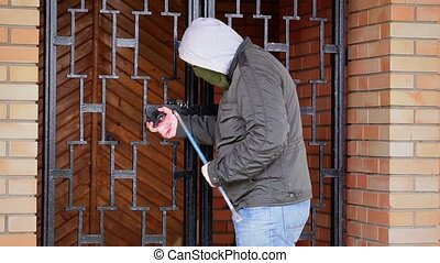 Robber with crowbar near the gates at outdoors