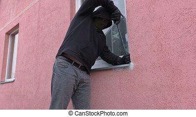 Robber with crowbar near window