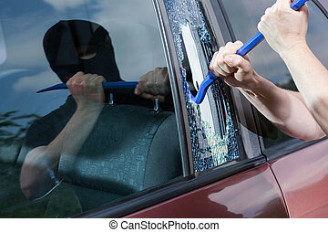Robber with crowbar smashing glass - Robber with crowbar...