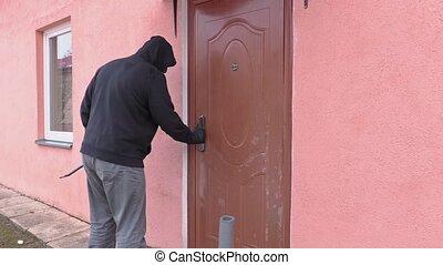 Robber with crowbar try to open door