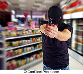 Robber with masked - Man in a mask with a gun in the...