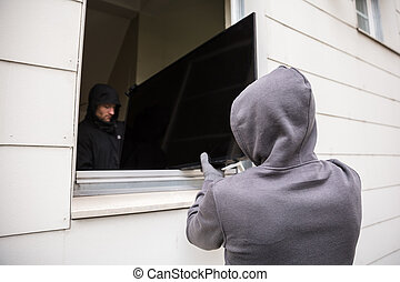 Robbers Stealing Television Through House Window