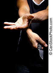 Robbery at Knifepoint - Close up of a robbers hands holding...