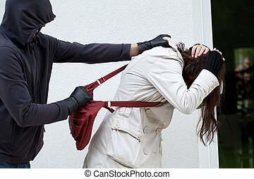 Robbery - Hooligan is assaulting a woman to attempt to steal...