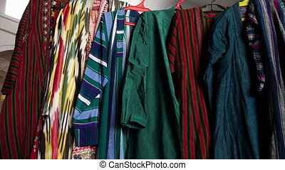 Steady, then handheld, panning, interior, medium close up shot of robes on hangers.