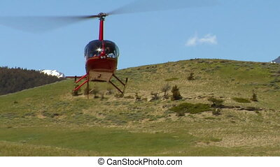 Robinson R 44 helicopter lands with snowy peaks in background