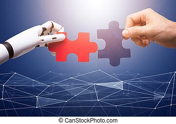 Robot And Man's Hand Joining Jigsaw Pieces