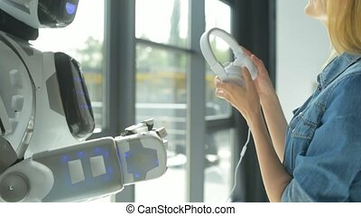Robot and young woman listening to music and dancing -...