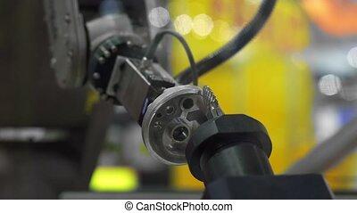 Robot arm holding car part closeup footage - Robot arm...