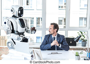 Robot-assistant is bringing beverage for smiling employee