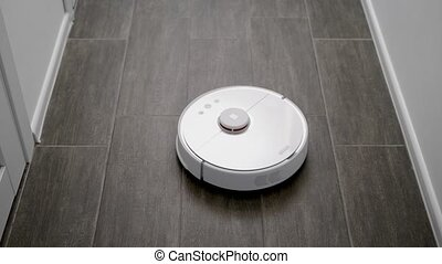 robot cleaner is moving over floor in a modern apartment,...