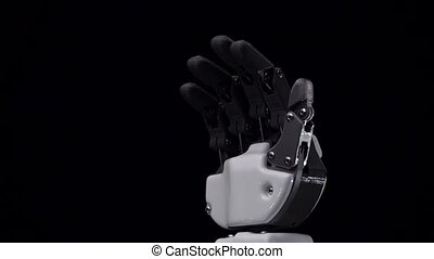 Robot hand close up waving goodbye . Black background. Close...