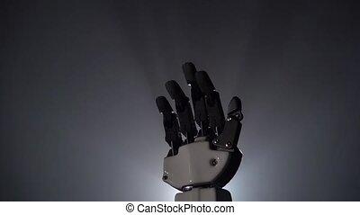 Robot hand close up waving goodbye. Black background. Close...