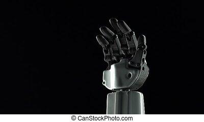 Robot hand close up waving goodbye. Black background. Slow...
