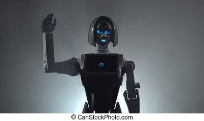 Robot hand waving bye. Black smoke background. Close up -...