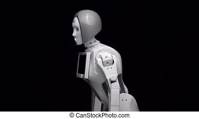 Robot leans forward. Black background. Side view - Robot is...