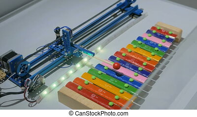 Robot playing on colorful xylophone at technology exhibition...