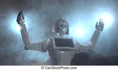 Robot raises her hands up. Black smoke background. Close up...
