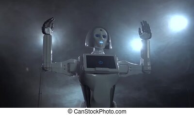 Robot raises her hands up . Black smoke background. Close...