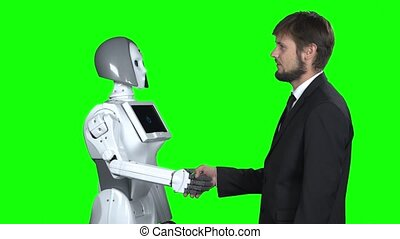 Robot shakes hands with a guy greets him. Green screen
