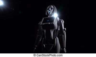 Robot stands and looks straight. Black background - Robot...