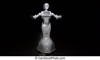 Robot talks and performs movements. Black background - Robot...