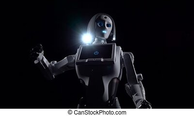 Robot talks and repeats various movements . Black background...