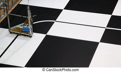 robot toy car moves along line drawn on large chessboard,...