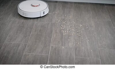 Robot vacuum cleaner in motion - White robot vacuum cleaner...