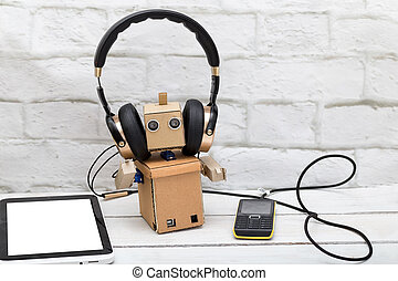 Robot with headphones listening to music from a mobile phone, lying beside the plate