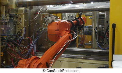 Robotic Arm in Factory - In a factory, a robotic arm grabs a...
