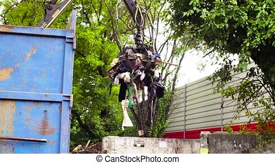 Robotic arm of garbage truck taking gabbage and putting it...