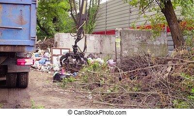 Robotic arm of garbage truck taking gabbage then putting it...