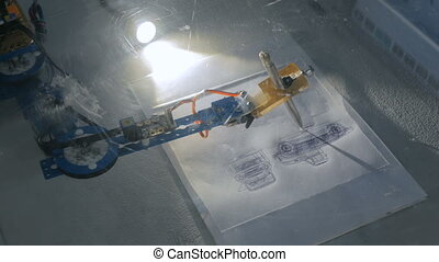 Robotic arm with pen drawing portrait at technology robotic...