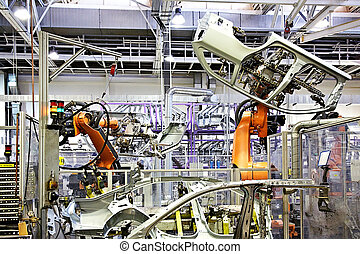 robotic arms in a car factory - robots in a car factory