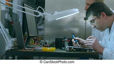 Robotic engineer assembling circuit board at desk 4k
