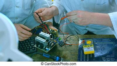 Robotic engineers examine circuit board at desk 4k