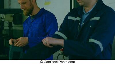 Robotic engineers wearing protective workwear in warehouse ...