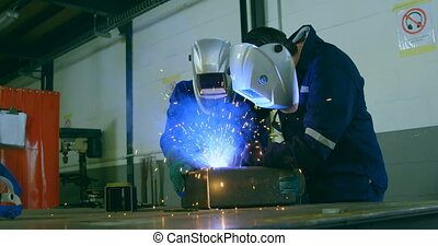 Robotic engineers welding metal in robotic warehouse 4k