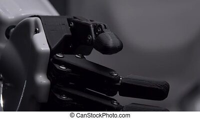 Robot's hand moves his fingers. Black background . Close up...