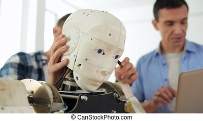 Robots head being modified by skilled constructor - Diligent...