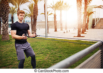 A photo of young, robust man exercising with resitance band at the park.
